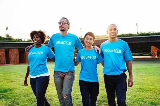 four person wearing blue shirts with volunteer print outdoors